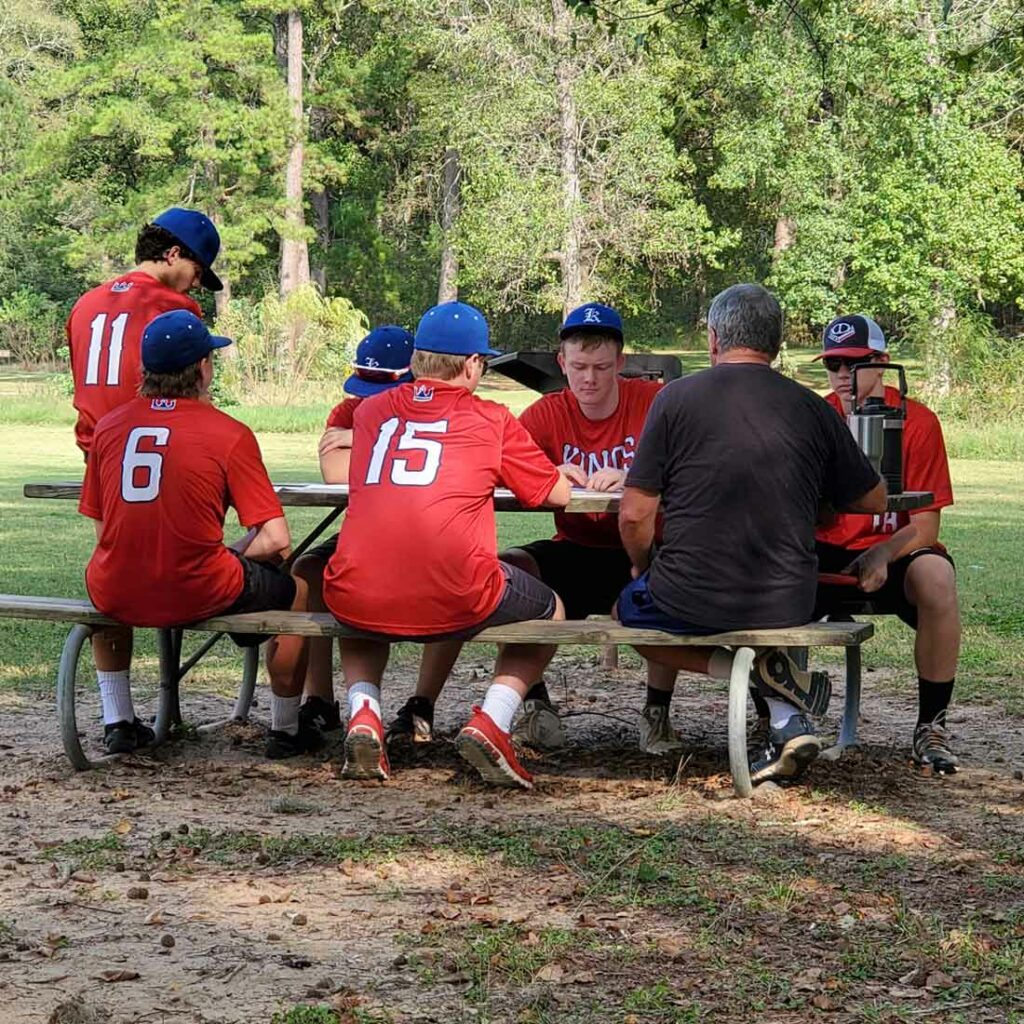 Tomball Kings baseball players studying at picnic table with one of their coaches. For homeschool athletes, the classroom is everywhere.